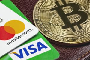 Visa, Mastercard credit cards and golden bitcoin with the leather wallet on the background. - Image