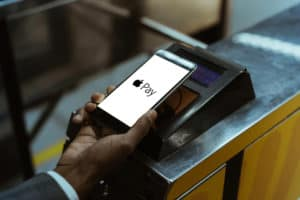 Close-up view of man using Apple Pay paying for public transport - Image