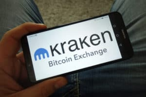 KONSKIE, POLAND - March 31, 2019 Man holding smartphone with Kraken cryptocurrency exchange logo - Image
