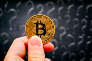Person hand with golden Bitcoin virtual money against blackboard with question marks. Close-up. - Image