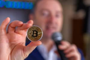 a man with a microphone holds bitcoin in his hand - Image