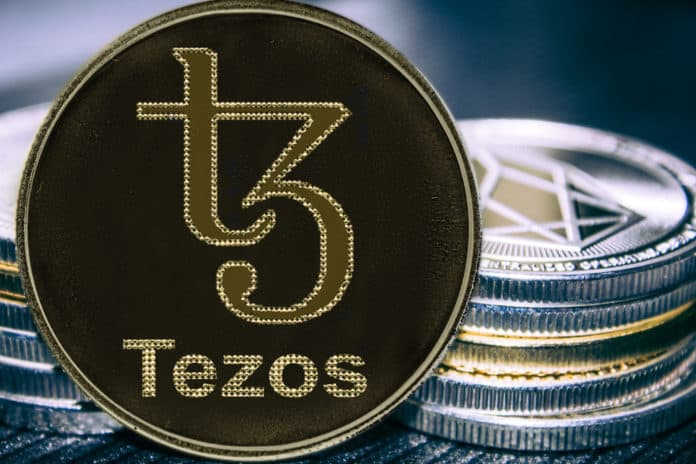 Coin cryptocurrency Tezos on the background of a stack of coins. XTZ coin. - Image