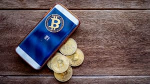 Lopburi, Thailandmung - May 4 2019 Mobile phone the screen is symbolic F (facebook) and digital money Bitcoin coin on the wooden floor. Concept Used about Facebook news and digital money. - Image