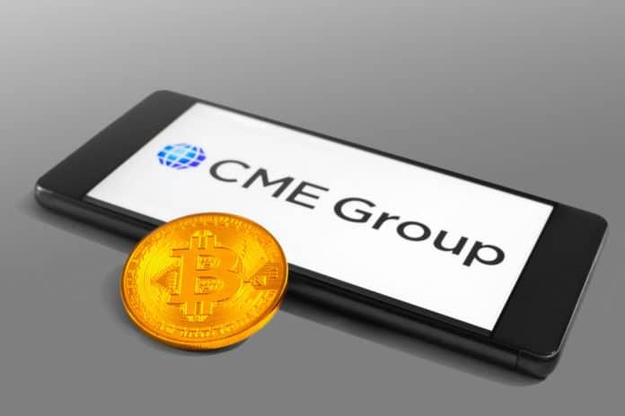 SLOVENIA - DECEMBER 16, 2018 CME Group logo on a mobile device with Bitcoin coin - Image